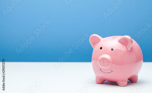 Fotografía  Pink piggy bank on a blue background. Copy space for text.