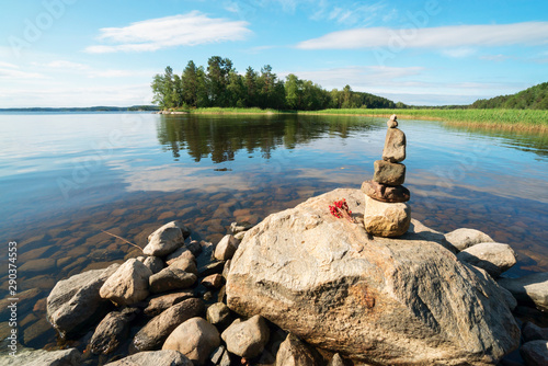 A small pyramid of stones and a bunch of strawberry berries on the shore of lake Ladoga Fototapet