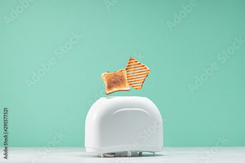 Foto Roasted toast bread popping up of toaster with green wall, front view