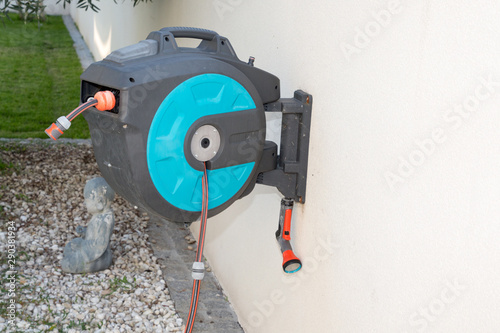 garden hose reel and spray gun fixed on the wall outdoors Canvas Print