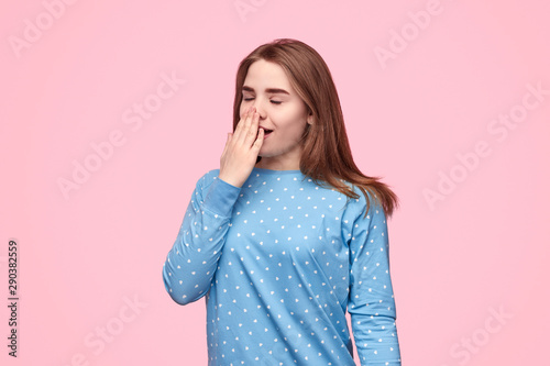 Fotografie, Obraz  Sleepy teen girl yawning and covering mouth