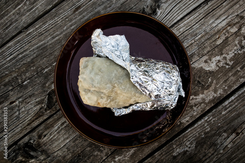 Fotografie, Obraz  California Style Burrito in Flour Tortilla Wrapped in Foil on Plate (Overhead)