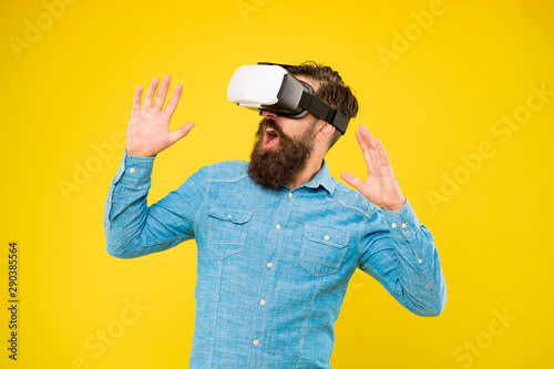 The game is on. Hipster play video game. Bearded man explore VR yellow background. Game developer or gamer. Be part of game with new virtual reality system. Gaming and entertainment
