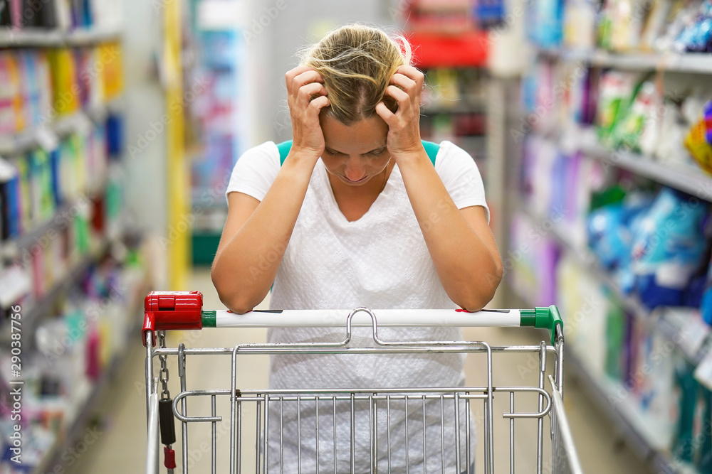 Fototapety, obrazy: Upset woman in a supermarket with an empty shopping trolley. Crises, rising prices for goods and products. Woman shopping at the supermarket.