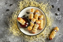 "Cute Sausages In The Dough ""Mummy"" With Ketchup And Spiders For The Halloween Party. Children's Food. Top View."