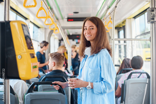 Obraz Stylish woman in blue shirt enjoying trip in the modern tram or bus, stands with cup of coffee in the public transport. - fototapety do salonu