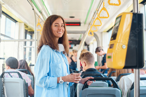 Fotografie, Obraz  Stylish woman in blue shirt enjoying trip in the modern tram or bus, stands with cup of coffee in the public transport