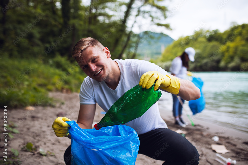 Fototapety, obrazy: Male teenager volunteer cleaning river shore