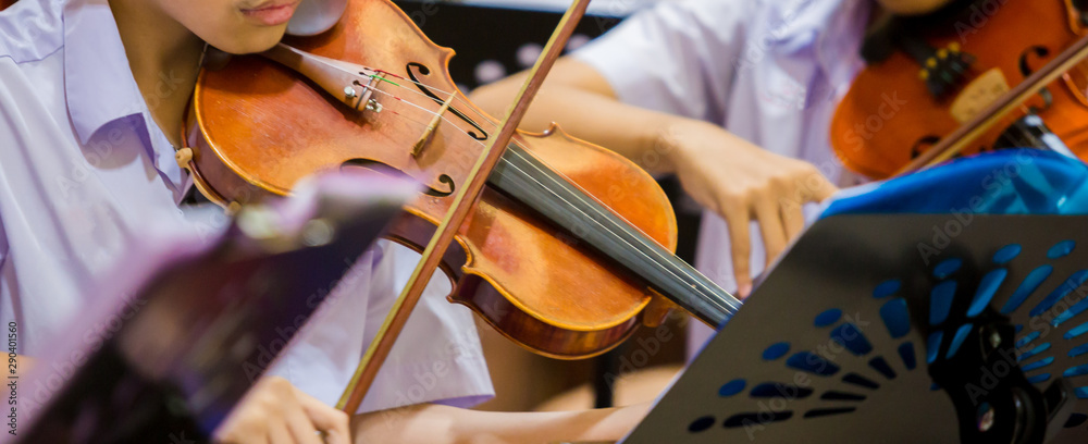 Fototapety, obrazy: Asian boy students playing violin with music notation in the group. Violin player. Violinist hands playing violin orchestra musical instrument closeup. Symphony orchestra on stage. Selective focus.