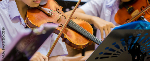 Asian boy students playing violin with music notation in the group. Violin player. Violinist hands playing violin orchestra musical instrument closeup. Symphony orchestra on stage. Selective focus. - 290401560