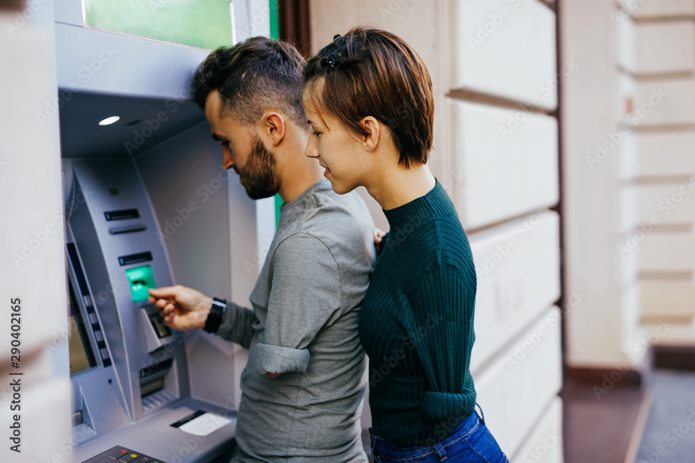 Fototapety, obrazy: Disabled couple usinig ATM machine in city street.