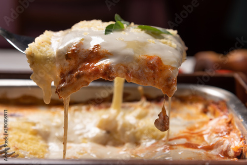 Obraz Delicious lasagna made with minced beef bolognese sauce and bechamel sauce topped with basil leaves, soft light - fototapety do salonu