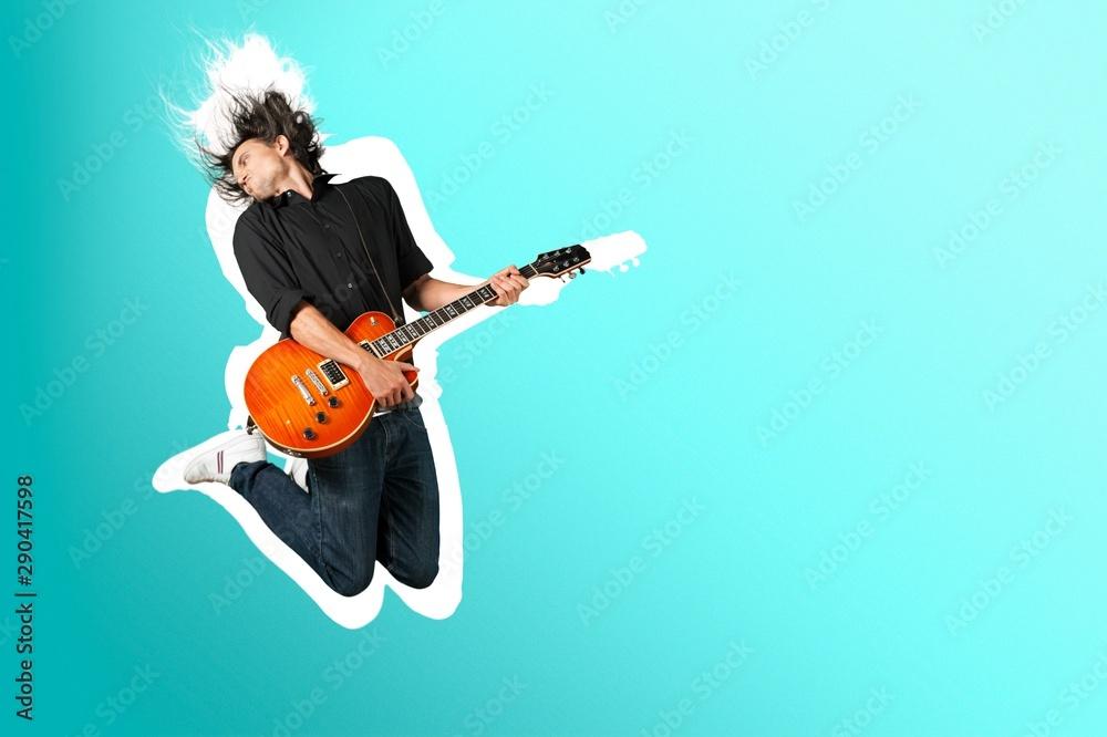 Fototapeta Male Guitarist playing music on grey wall background