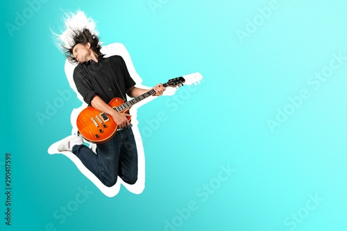 Male Guitarist playing music on grey wall background