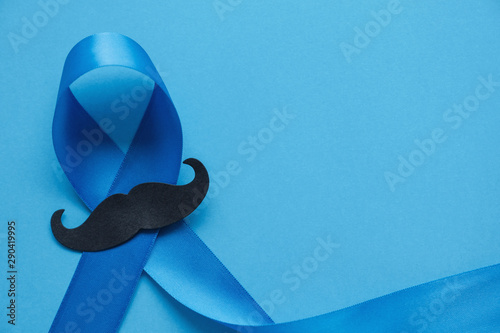 Photo  Light blue ribbon with mustache on blue background , Prostate Cancer Awareness,
