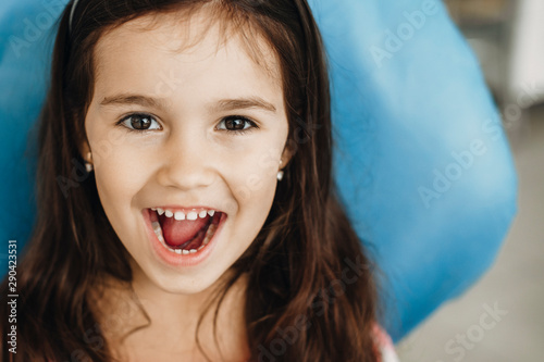 Close up portrait of a cute little girl showing teeth after surgery in a pediatric clinic. Happy little kid after teeth examination.