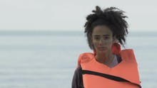 Bruised Afro-American Girl In Life Vest Looking At Camera, Plane Crash Victim