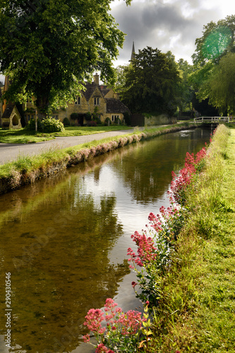 Pink flowers on the banks of the River Eye in morning sun in Lower Slaughter Cot Tablou Canvas