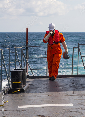 Fényképezés Deck Officer on ship , wearing personal protective equipment, holds VHF radio in hands