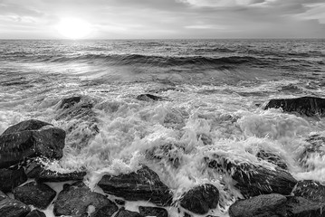Fototapeta Wschód / zachód słońca The stunning black and white seascape with the sky and water foam at the rocky coastline of the Black Sea