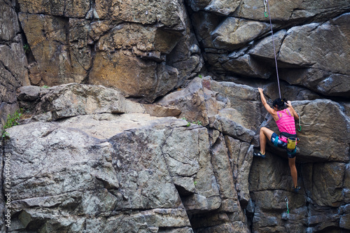 Fotografie, Tablou The girl climbs the granite rock.