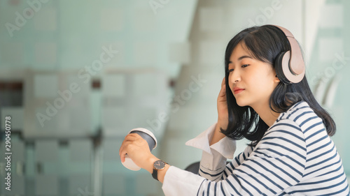 A beautiful Asian woman listening to music with headphone while drinking coffee with feeling happy and relax in cafe - 290450778