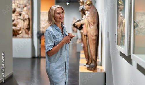 Foto  Mature woman visitor in the historical museum looking at pictures