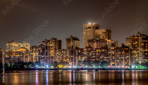 Fototapeta Mesmerizing photo of Colaba Skyline at night, as seen from Nariman Point of Marine Drive. Buildings, Roadside and Night Market Light reflections may be seen in calm Arabian Sea, is like cherry on top obraz