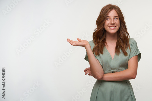 Fototapety, obrazy: Indoor portrait of happy lovely young readhead female looking aside with charming smile, pointing away with raised palm, posing over white background