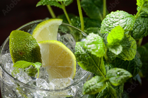 Fototapeta  Glass with ice, mint leaves and lime slices.