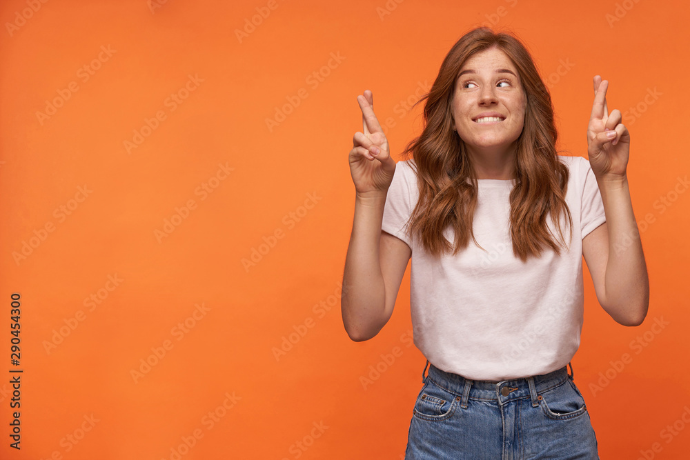 Fototapeta Studio photo of charming young redhead woman with hairstyle waring casual clothes, keeping her fingers crossed for good luck, hoping for better