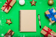 canvas print picture - Notebook with a clean page and Christmas-tree decorations, New Year's toys and gift boxes, green background. Concept of preparation and planning for Merry Christmas and New Year. Flat lay, top view