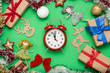 canvas print picture - Red alarm clock, Christmas decorations, Christmas toys and gift boxes on a green background. The concept of Merry Christmas and New Year. Flat lay, top view