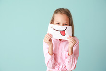 Little Girl Hiding Mouth Behind Drawn Smile On Color Background