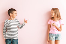 Portrait Of Happy Little Children Pointing At Each Other On Color Background