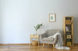 Leinwanddruck Bild Stylish interior of room with armchair and eucalyptus branches in vase on table