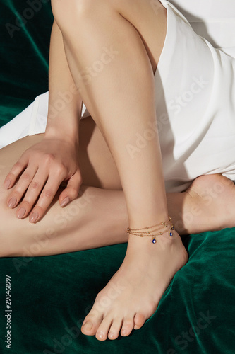 Cropped shot of a lower body part of a girl, sitting on a green velvet background Canvas Print