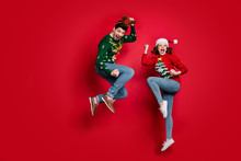 Full Body Photo Of Amazed Jumping Couple Excited By X-mas Prices Wear Ugly Ornament Jumpers And Headwear Isolated Red Color Background