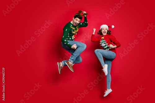 Spoed Fotobehang Kerstmis Full body photo of amazed jumping couple excited by x-mas prices wear ugly ornament jumpers and headwear isolated red color background