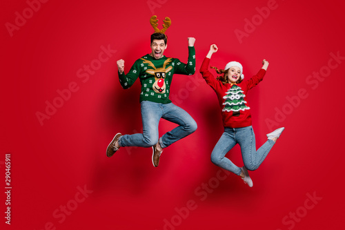 Spoed Fotobehang Kerstmis Full size photo of funky lady and guy jumping excited by x-mas prices wear ugly ornament jumpers and headwear isolated red color background