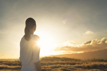 Looking to the future, new day, new beginning. Young female standing on a mountain facing sunset.