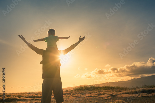 Fotografie, Obraz  Father son having fun outdoors at sunset pretending to fly