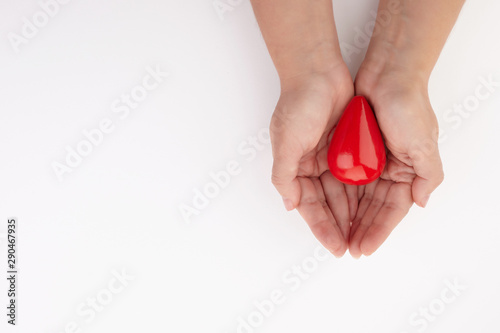 Fotografie, Obraz  Two hands holding red blood drop on white background