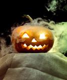 Halloween pumpkin head jack-o-lantern with scary evil face. Seasonal illuminated decoration. Looks scary, neon light, white smoke and dark background. Holidays. Black friday, sales. Night of fear.