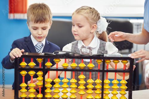 teacher teaches children mental arithmetic using large abacus soroban Canvas Print