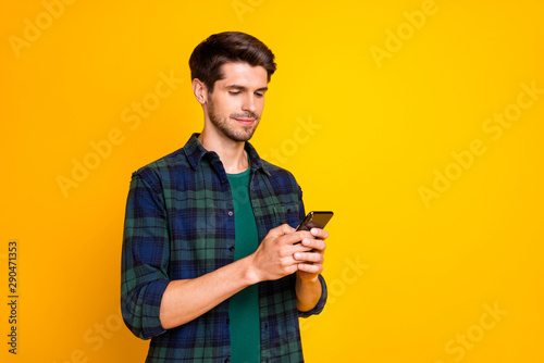 Photo of blogger guy holding telephone in hands checking subscribers wear casual Fototapeta
