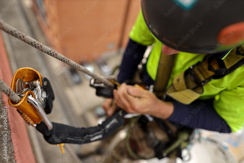 Fototapety, obrazy: Rope access inspector industrial abseiler wearing full body safety abseiling harness  using self controller stop fall descent safety backup device energy absorbing lanyard attached while abseiling