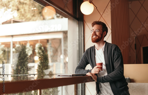 Fotografie, Obraz  Glad man relaxing in cafe with drink