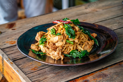 Photo  Stir Fry spaghetti with chicken and hearbs in black bowl