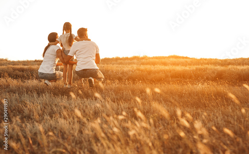 Anonymous family enjoying sunset in countryside Wallpaper Mural
